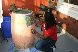At the Mt. Airy Art Garage, artist Barbara Kigozi decorates a rain barrel for use along Germantown Avenue in Mt. Airy. | Photo: courtesy of Mt. Airy BID