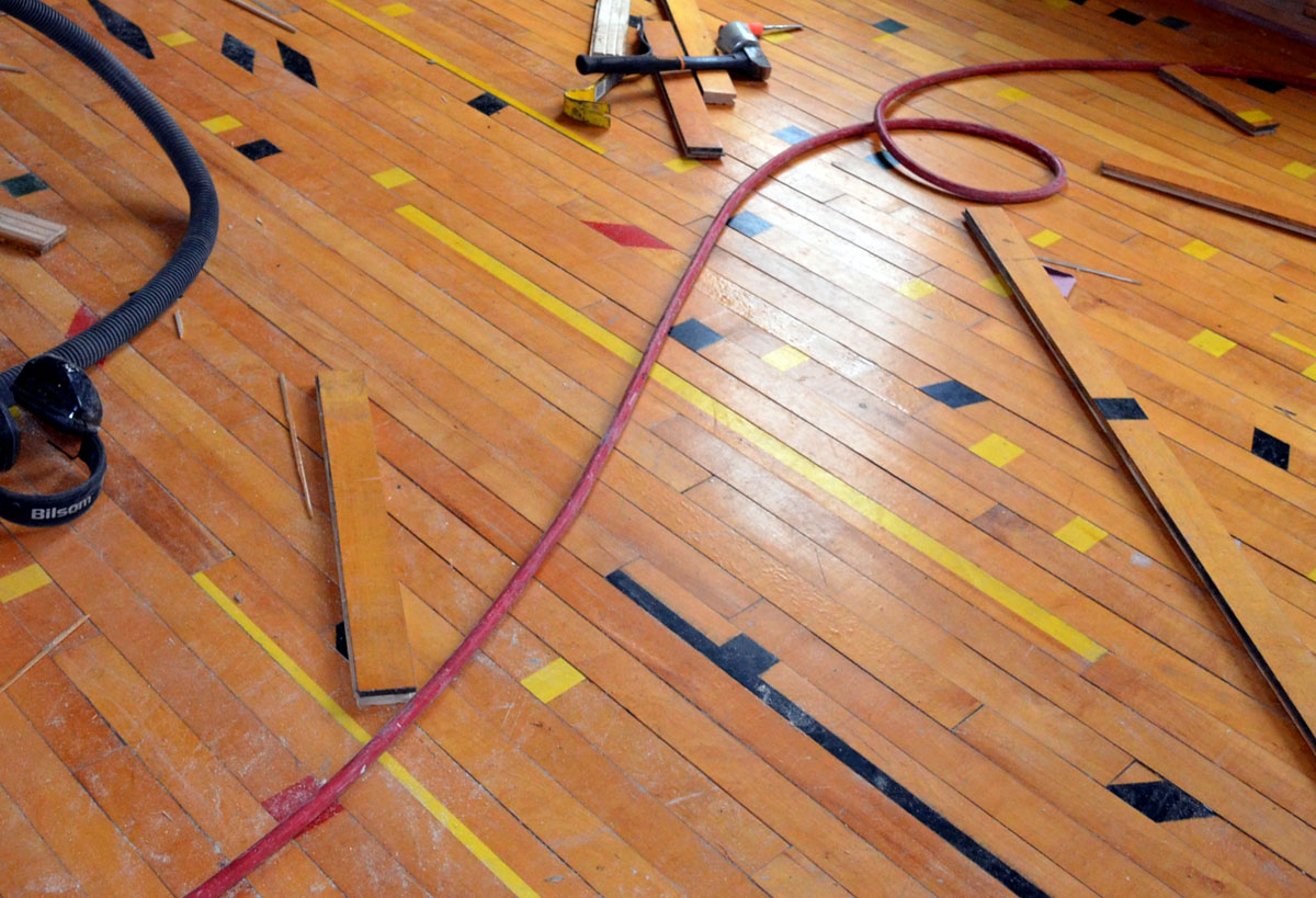 A glimpse at the finished project. Because the flooring was shuffled during relocation like a deck of cards, and laid down again at random, it now makes a whimsical scene: the neat basketball court lines have been exploded into little zips of red, black, and green, across the expanse of each room. Some have called it Russian Constructivist; others simply say it looks like confetti. | Photo: Jacob Hellman