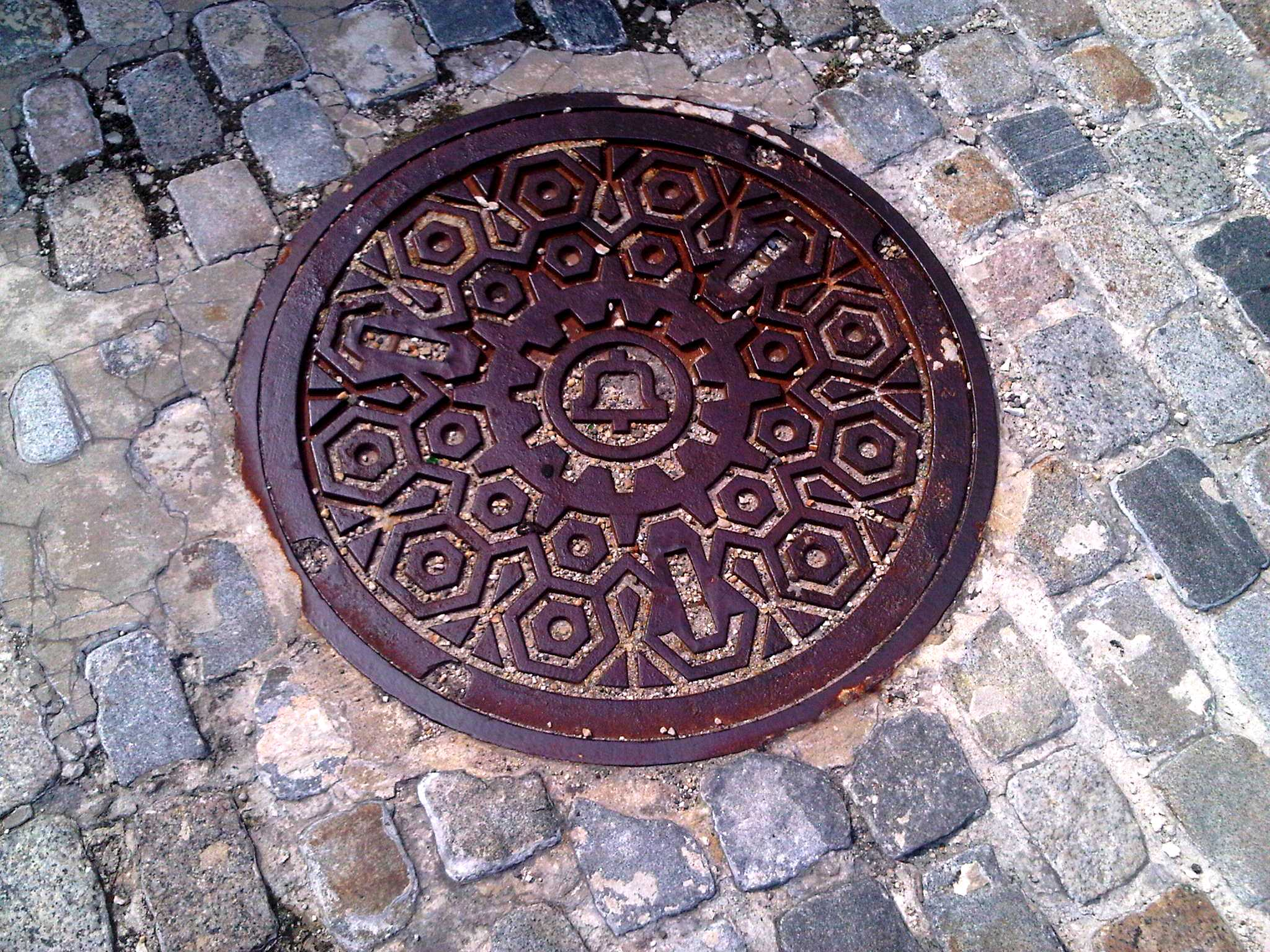 A Bell Telephone Company manhole cover along a street in Old City Philadelphia.