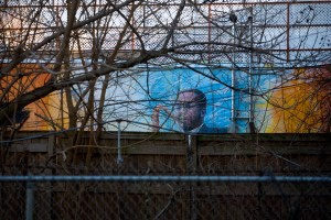 A mural of John Coltrane in his former back yard peeks over neighboring fences | Photo: Bradley Maule