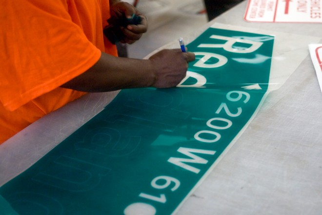 Before they're mounted for 7-10 years in public, street signs first come off a plotter from a roll of vinyl, and letters are removed by hand before the shape is mounted to the retroreflective metal sign | Photo: Bradley Maule