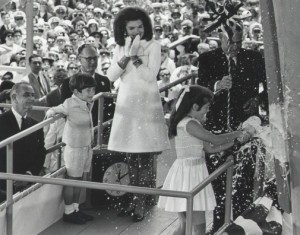 Nine-year-old Caroline Kennedy christens the aircraft carrier named for her father with champagne, while President Lyndon B. Johnson and Caroline's mother Jackie and brother John-John watch | Photo: 1967 AP Wire photo