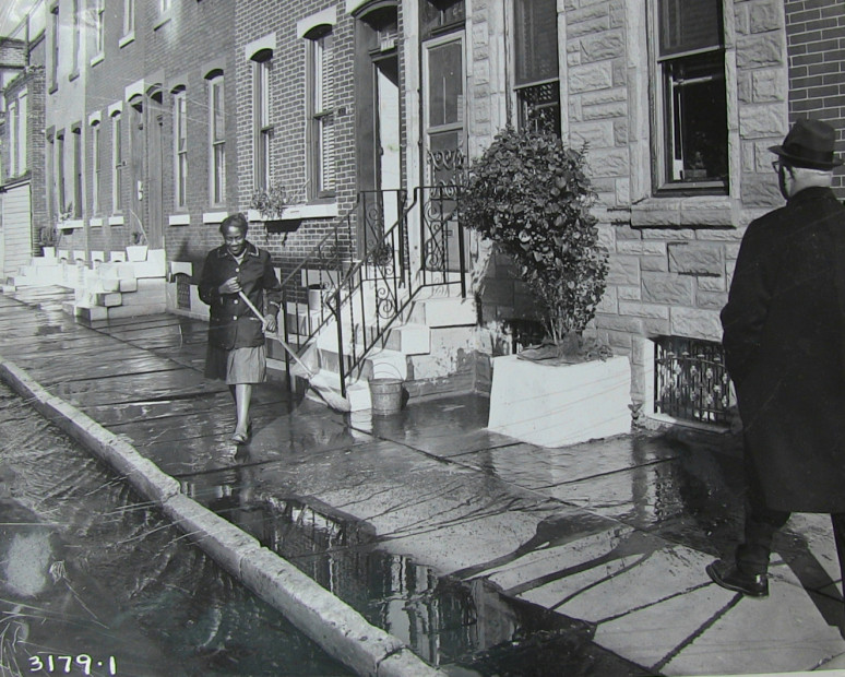 """Mrs. Alma Thomas cleans her sidewalk on the 2400 block of Sharswood Street as then-mayor James H.J. Tate walks down the block. (Photo courtesy of Talmadge Belo)"""