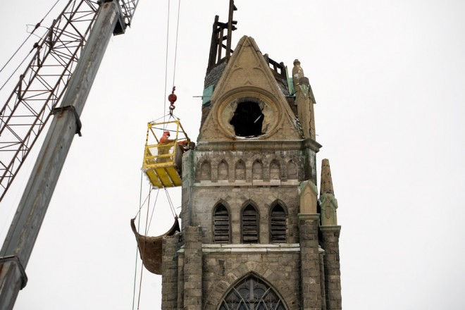 Workers in a cage dangling from a crane steady the cage and use a handheld jackhammer to remove pieces of the stone church | Photo: Bradley Maule