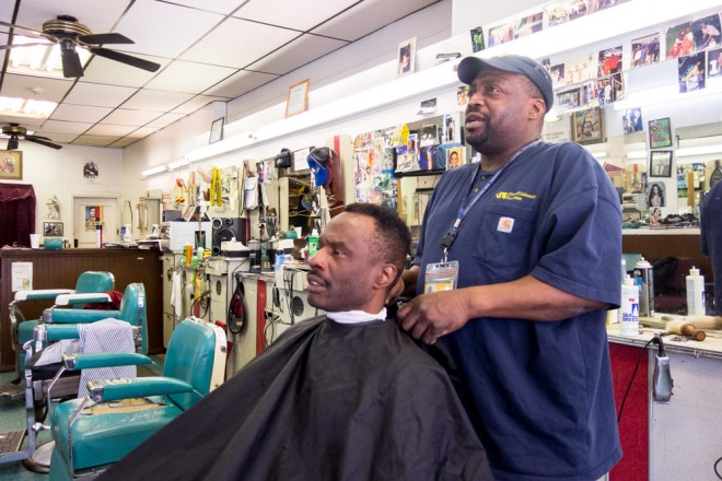 Troy Yancey tightens up friend and customer Ron Tolbert's fade inside Ali's Barber Shop | Photo: Theresa Stigale