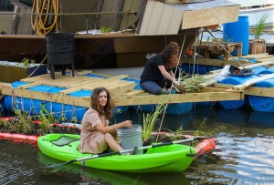 Artist Mary Mattingly kayaks around the garden while Karla Stingerstein preps another planter | Photo: Michael Bixler