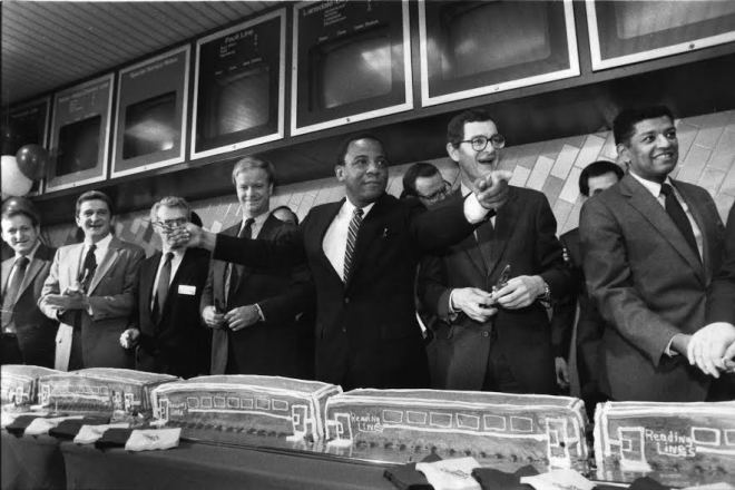"""""""Mayor Goode points to the baker of the train cake after it was noticed there were no women at the cake cutting""""   Photo: Philadelphia Inquirer collection at Temple Urban Archives via History Making Productions"""