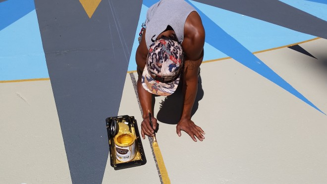 "Mural Arts painter adds gold stripe to ""correct"" the city's compass 
