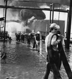Firemen pulling hoses through water to reach Gulf Oil refinery fire 1975