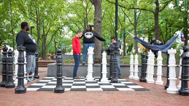 """From left to right: Alexander Williams, Matt Forrest, Jessica McNeil, and Dennis Elwell play a game of chess at Spruce Street Harbor Park."" 