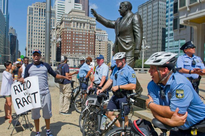 """Black Lives Matter member Asa Khalif berates officers after a Klan hood he placed atop the head of the Frank Rizzo statue was removed outside the Municipal Services Building."" 