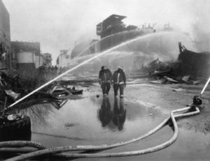 Firemen walk under spraying hose directed toward burning remains of the Publicker Industries factory Source: Firemen walk under spraying hose directed toward burning remains of the Publicker Industries factory, 1992 | Source: George D. McDowell Philadelphia Evening Bulletin Collection, Special Collections Research Center, Temple University Libraries