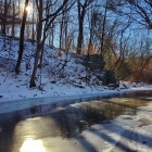 The sun peeks over Morris Arboretum's Tree Adventure and the frozen Wissahickon Creek