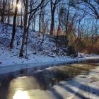 The sun peeks over Morris Arboretum's Tree Adventure and the frozen Wissahickon Creek