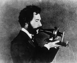 A young Alexander Graham Bell holding his invention.