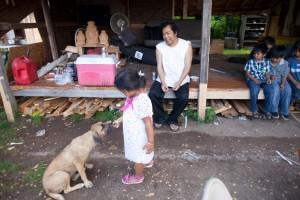 A young girl feeds a dog meat scraps | Photo: Dan Papa