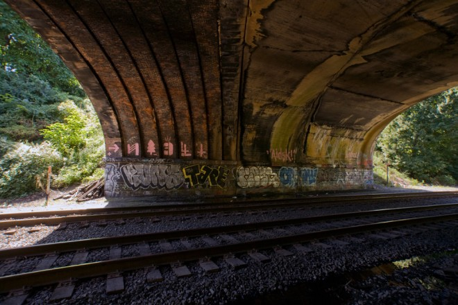 Under the PRR/Amtrak bridge, one can see the original skew arch bridge and the later concrete addition to accommodate extra tracks | Photo: Bradley Maule