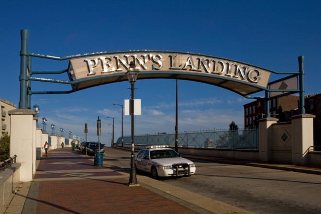 "The photographer was upset that the street lamp abuts the ""Penn's Landing"" arch too, but it was the best angle for the sunburst glints on the sign 