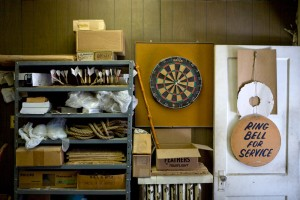 Keep your enemies close: an English style board hangs in Widdy Darts' Kensington shop; on the shelf are a number of untrimmed darts | Photo: Bradley Maule