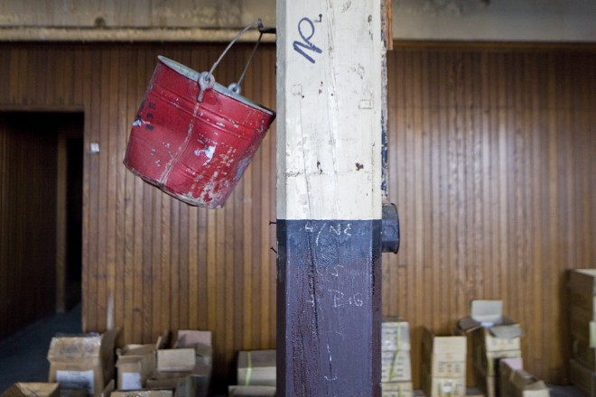 A fire bucket. There once would have been dozens of them filled with sand throughout the building. | Photo: Peter Woodall