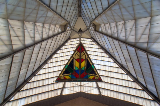 "The hues of a plexiglass chandelier over the center of the Main Auditorium amplify Frank Lloyd Wright's decision to use a glass roof, ""since this is to be God's temple, I prefer to have Him color the glass"" 