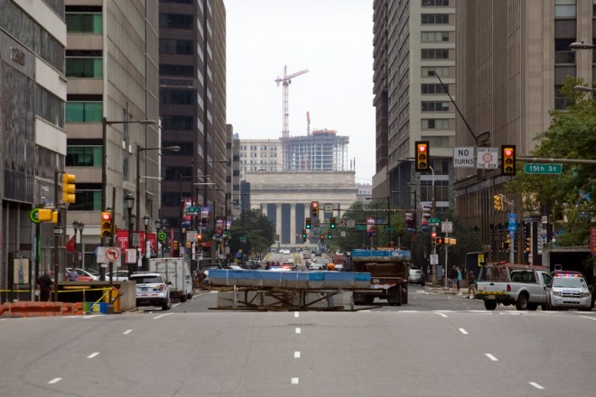 The N sits in the middle of JFK Boulevard awaiting placement on the truck that will carry it away; Lancaster Square's construction rises above 30th Street Station in the distance | Photo: Bradley Maule