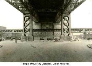 The El in its original configuration under Benjamin Franklin Bridge at Front Street (looking east). This place is close to the transition portal near Arch Street. Interstate 95 goes through this site now, with the elevated in the median. From Temple University Urban Archives.