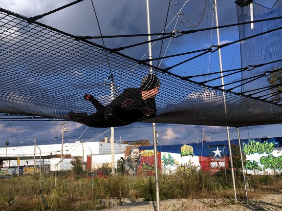 """A trapeze student falls into the protective netting at Fly School Circus Arts."" 