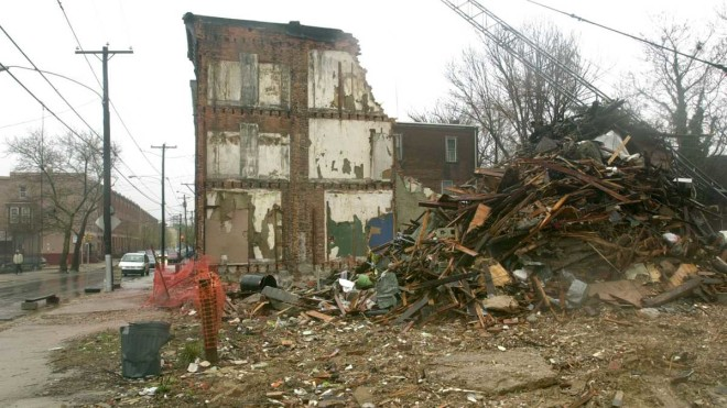 """An abandoned row house is seen next to a vacant lot full of rubble in North Philadelphia this file photo. In 2001, the city launched a plan to spend $295 million to tear down 14,000 abandoned homes, renovate 2,500 buildings and clear 31,000 vacant lots."" 