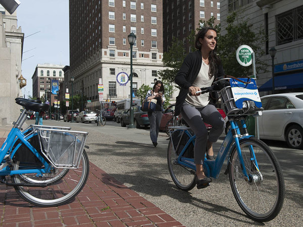 """Tara Jennings rides an Indego bike home from work in Philadelphia. About 500 bikes are now available, with an immediate target of 650 to 700, and three more stations will soon open."" 