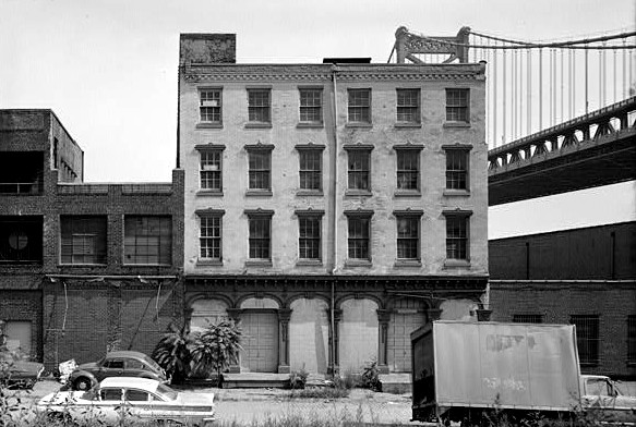 The rear façade of the abandoned Brock Stores before the 1977 fires that destroyed the building. The cast iron arches, columns and other cast iron pieces eventually made it to the Smithsonian Institution. The Ben Franklin Bridge is in the background | HABS, Library of Congress