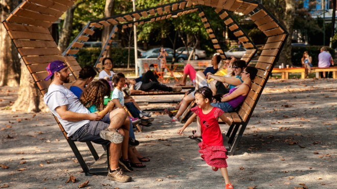 """People chatting (and playing) on Looped In benches at Clark Park in Philadelphia."" 