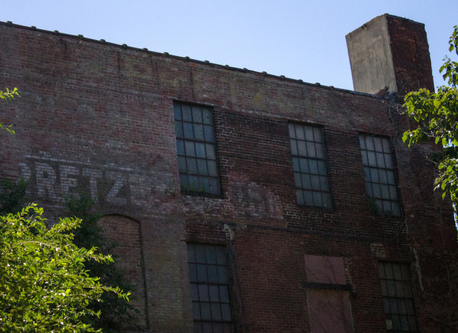 A ghost sign lurks in the shadows of the west-facing wall of the former pretzel factory. | Photo: Michael Bixler