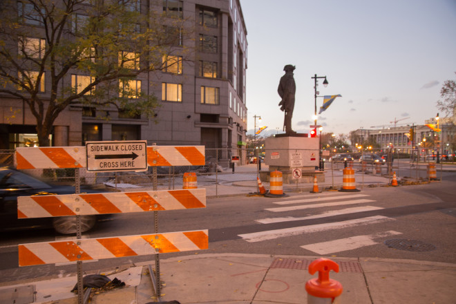 """""""Gates close off what was once the Four Seasons Hotel and signs redirecting pedestrians."""" 