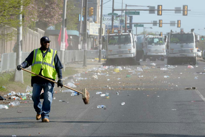 """A Streets Department worker begins cleanup near the starting line at Broad & Olney after some 40,000 runners had taken off for the Navy Yard in May. The Broad & Olney intersection is cited as one of the most dangerous for pedestrians in Philadelphia."" 