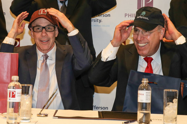 """""""At the signing table (from left): Stephen Klasko MD MBA President and CEO, Jefferson, and Stephen Spinelli, Jr., PhD, President, Philadelphia University, trade ball caps after signing the agreement."""" 