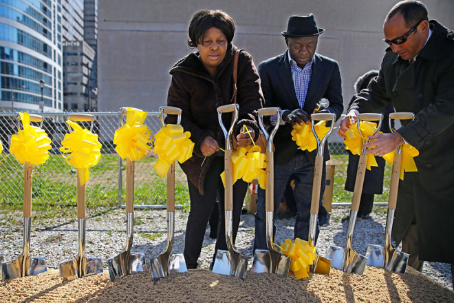 """Kadie Conteh, left, and Aiah Boya, center, the sister and husband of Roseline Conteh—who died in the Salvation Army building collapse at 22nd and Market—tie yellow ribbons around the shovels that will be used to break ground on the memorial at the site."" 
