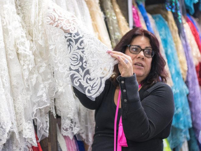 Sherie Abrams showing wedding gown lace to a customer at Jack B's | Photo: Theresa Stigale